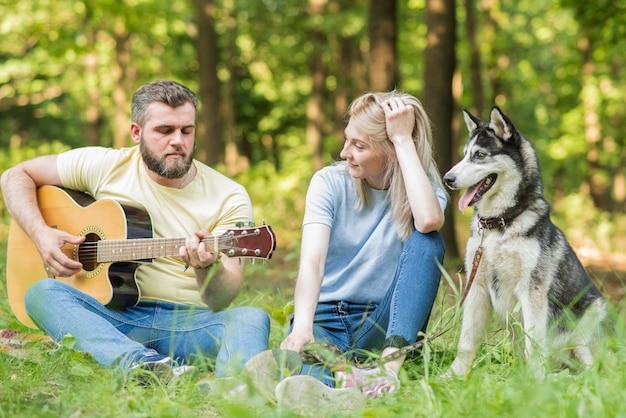 Jong en mooi paar ontspannen in de natuur met een hond op de gitaar