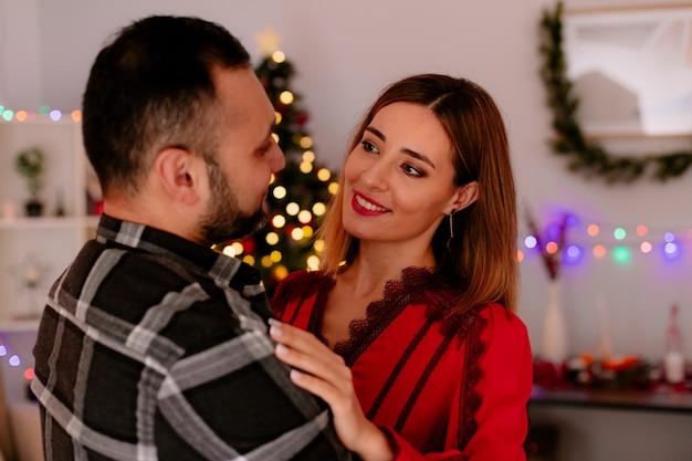 Jong en mooi paar zittend op een bank gelukkig verliefd omarmen samen kerst vieren in ingerichte kamer met kerstboom op de achtergrond