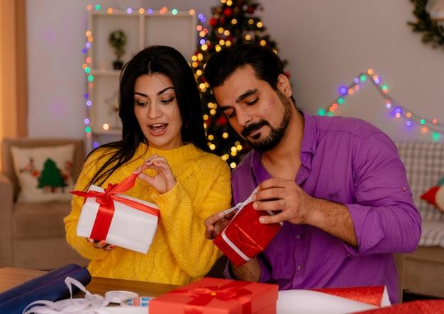 Jong en mooi stel man en vrouw blij en verrast met geschenken aan tafel in een met kerst versierde kamer met kerstboom in de muur
