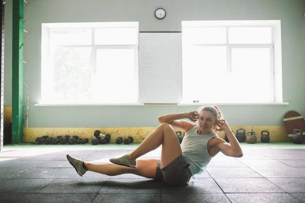Jong en sterk meisje met een glimlach die oefeningen voor de spieren van de maag doet, drukt op de vloer in de sporen