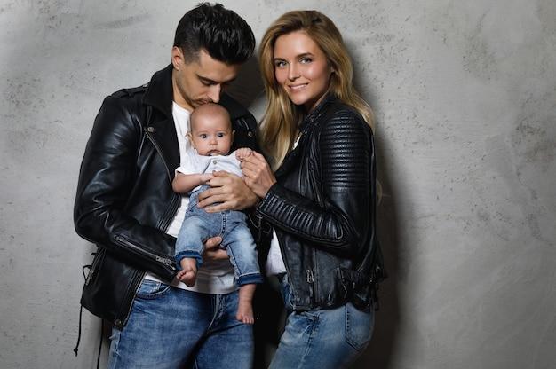 Jong en stijlvol gezin. gelukkige moeder en vader met kleine baby.