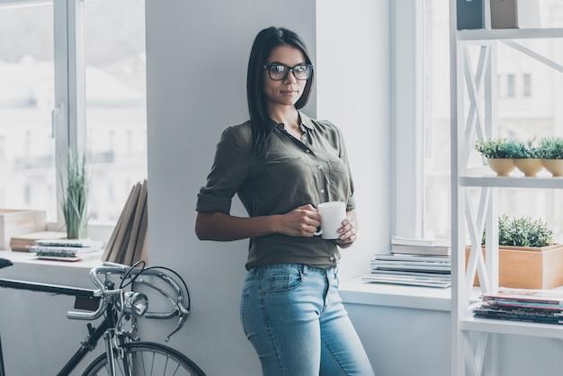 Jong en succesvol. aantrekkelijke jonge vrouw in slimme vrijetijdskleding die een koffiekopje vasthoudt en naar de camera kijkt terwijl ze in de buurt van het raam op kantoor staat