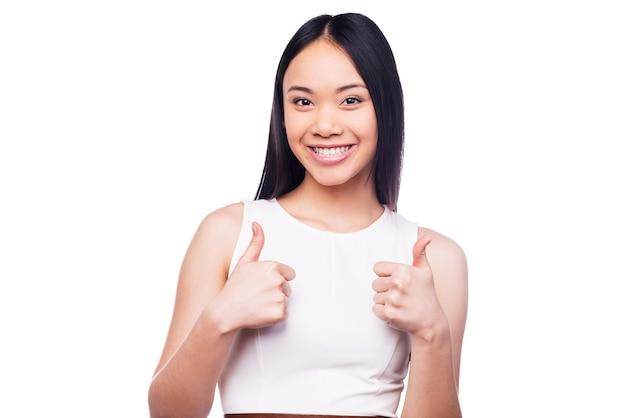 Jong en succesvol. mooie jonge aziatische vrouw die naar de camera kijkt en haar duimen laat zien terwijl ze tegen een witte achtergrond staat