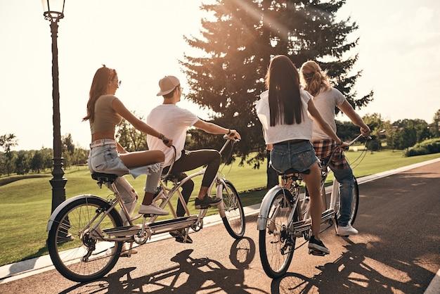 Jong en vol energie. groep jongeren in vrijetijdskleding die samen fietsen terwijl ze zorgeloze tijd buitenshuis doorbrengen