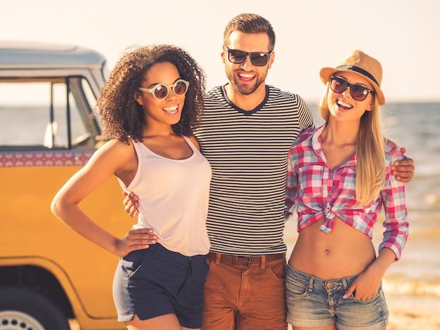 Jong en zorgeloos. vrolijke jonge man die twee vrouwen omhelst terwijl hij aan de kust staat met een retro minibusje op de achtergrond