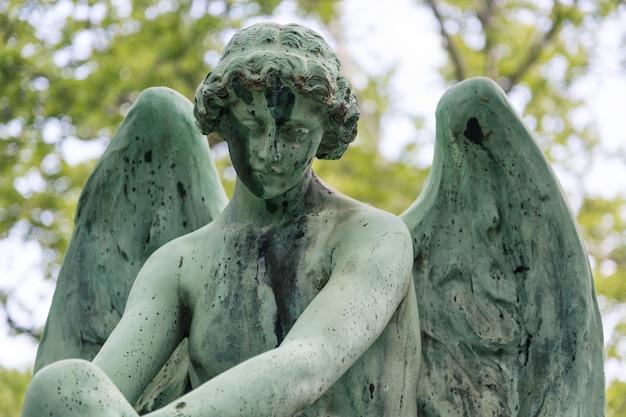 Jong engelenbeeldhouwwerk op een graf bij een kerkhof