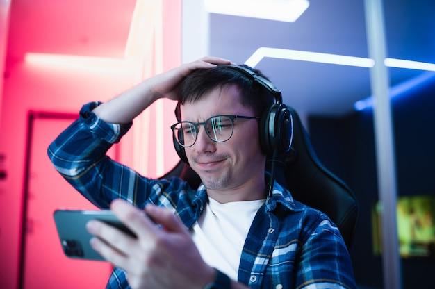 Jong esport-gamermeisje voelt zich boos tijdens het spelen van een online videogame op zijn smartphone omdat het internet niet werkt.