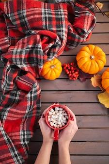 Jong europees meisje met rode manicure op nagels houdt in handen rode kop koffie met marshmallows