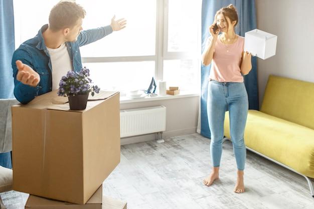 Jong familiepaar kocht of huurde hun eerste kleine appartement. guy geïrriteerd