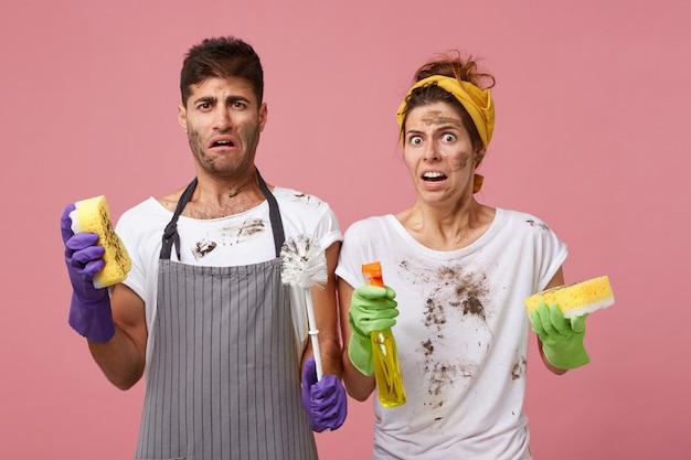 Jong familiepaar met vuile gezichten die walgelijk kijken met glazenwasser en sponzen die ramen in de woonkamer wassen. mannen en vrouwen die hun werk over huis met een slecht humeur voltooien