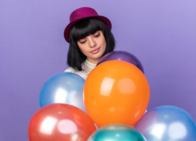 Jong feestmeisje met een feestmuts die achter ballonnen staat en naar hen kijkt, geïsoleerd op een paarse muur