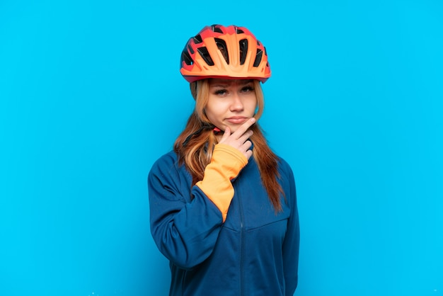 Jong fietsermeisje dat bij het blauwe denken wordt geïsoleerd als achtergrond