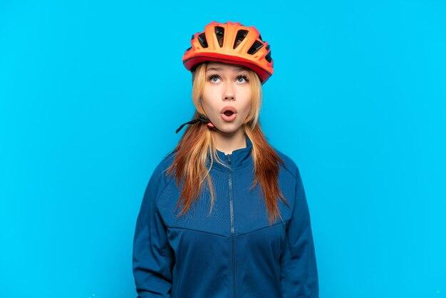 Jong fietsermeisje dat op blauwe achtergrond wordt geïsoleerd die omhoog en met verbaasde uitdrukking kijkt