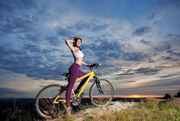 Jong fietserwijfje op fiets bovenop berg met mooi landschap bij zonsondergang