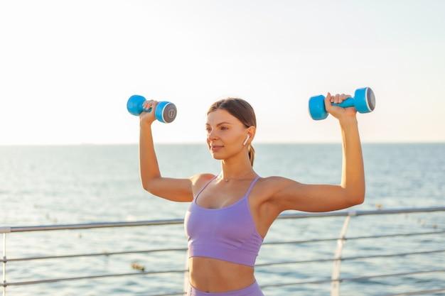 Jong fit vrouw oefenen oefening met halters op het strand bij zonsopgang. ochtendtraining met losse gewichten