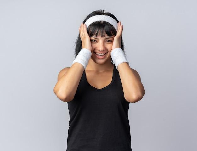 Jong fitnessmeisje dat een hoofdband draagt en naar de camera kijkt, vrolijk en vrolijk glimlacht terwijl hij over wit staat