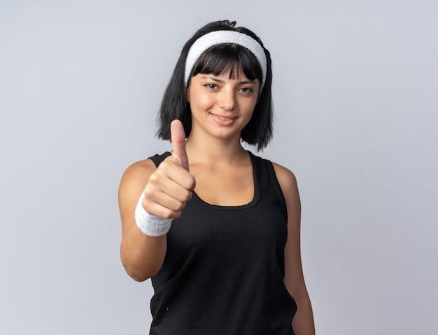 Jong fitnessmeisje dat een hoofdband draagt en naar een camera kijkt die zelfverzekerd glimlacht en duim toont terwijl hij over wit staat