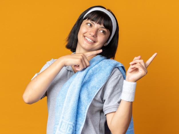 Jong fitnessmeisje dat een hoofdband met een handdoek op haar schouder draagt en gelukkig opzij kijkt