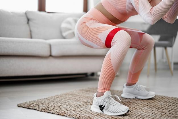 Jong fitnessmeisje dat sportoefeningen doet in haar woonkamer thuis