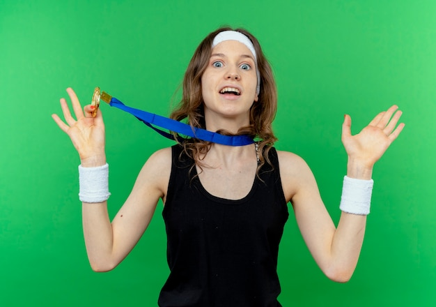Jong fitnessmeisje in zwarte sportkleding met hoofdband en gouden medaille om hals verrast en verbaasd over groen