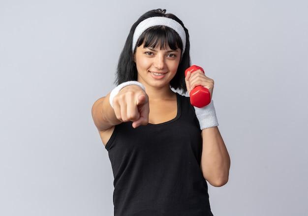 Jong fitnessmeisje met een hoofdband die een halter vasthoudt en oefeningen doet die er zelfverzekerd uitzien
