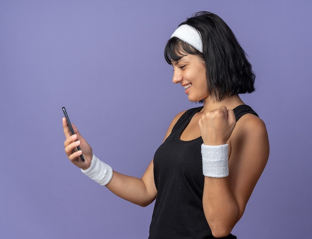 Jong fitnessmeisje met een hoofdband die een smartphone vasthoudt en ernaar kijkt, blij en opgewonden, gebalde vuist die over blauw staat