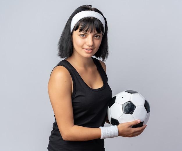 Jong fitnessmeisje met een hoofdband die een voetbal vasthoudt en naar een camera kijkt die zelfverzekerd glimlacht en over wit staat