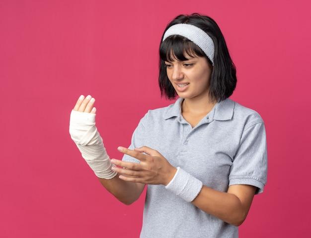 Jong fitnessmeisje met een hoofdband die haar verbonden hand aanraakt en er onwel uitziet en pijn voelt