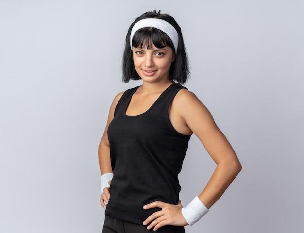 Jong fitnessmeisje met een hoofdband die naar de camera kijkt en zelfverzekerd glimlacht terwijl ze over wit staat