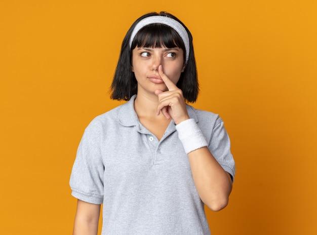 Jong fitnessmeisje met een hoofdband die opzij kijkt en verbaasd haar neus sluit met een vinger