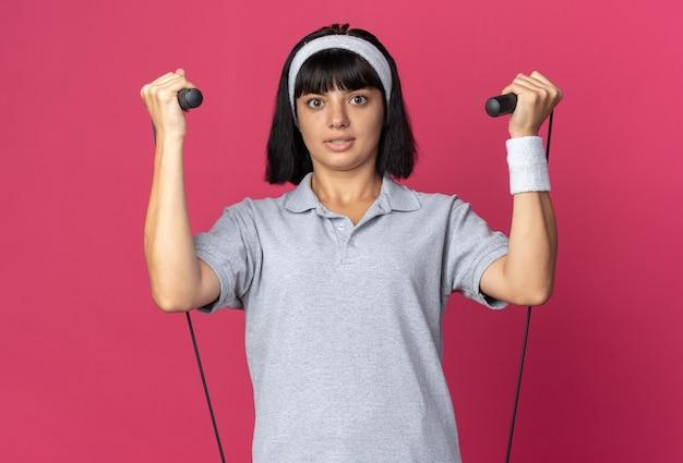 Jong fitnessmeisje met een hoofdband die springtouw vasthoudt en gaat springen en er verward uitziet terwijl ze over een roze achtergrond staat