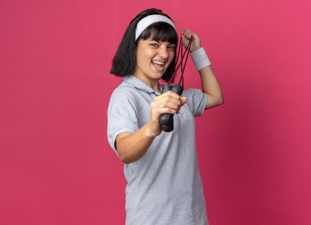 Jong fitnessmeisje met een hoofdband die springtouw vasthoudt en naar de camera kijkt, blij en vrolijk glimlachend over roze achtergrond