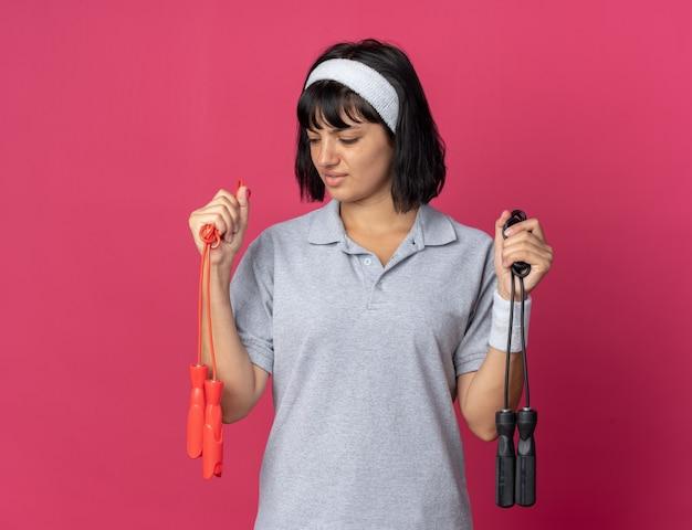 Jong fitnessmeisje met een hoofdband die springtouwen vasthoudt en er verward uitziet terwijl ze probeert een keuze te maken