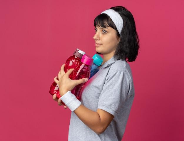 Jong fitnessmeisje met een hoofdband die waterflessen vasthoudt en verward opzij kijkt terwijl ze over een roze achtergrond staat