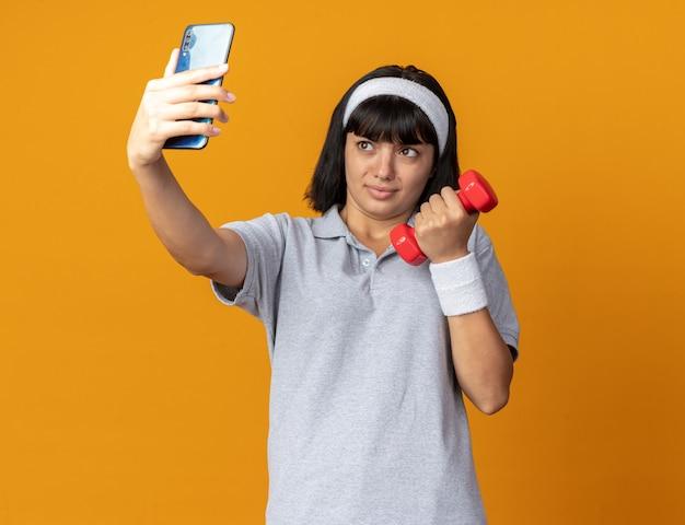 Jong fitnessmeisje met een hoofdband met een dumbbell die selfie maakt met een smartphone en er verward uitziet terwijl hij over oranje staat