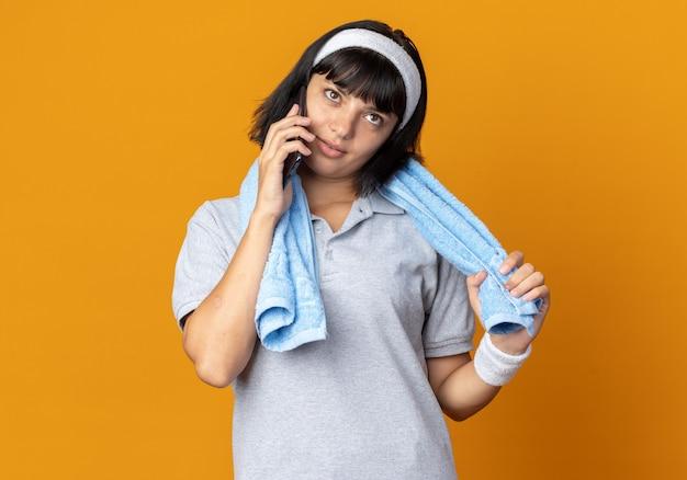 Jong fitnessmeisje met een hoofdband met een handdoek om haar heen glimlachend zelfverzekerd terwijl ze op een mobiele telefoon praat die over een oranje achtergrond staat