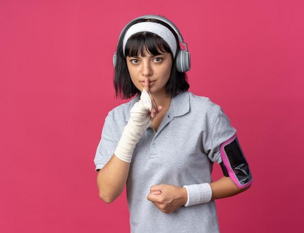 Jong fitnessmeisje met een hoofdband met een koptelefoon en een armband voor een smartphone die een stiltegebaar maakt met de vinger op de lippen en er zelfverzekerd uitziet