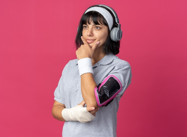 Jong fitnessmeisje met een hoofdband met een koptelefoon en een armband voor een smartphone die opzij kijkt met een peinzende uitdrukking op het gezicht