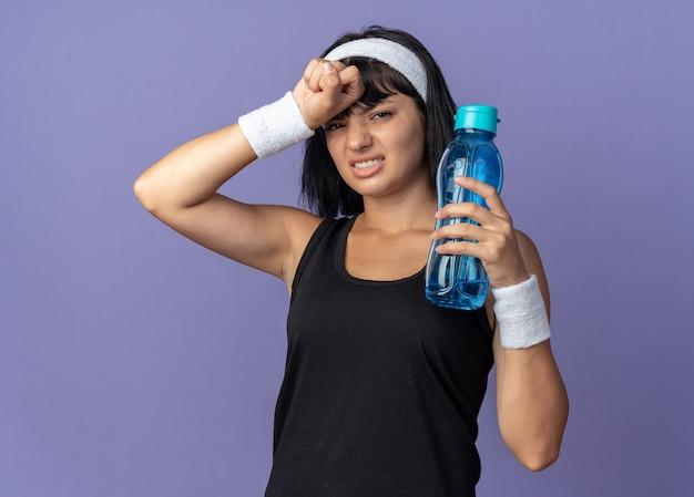 Jong fitnessmeisje met een hoofdband met een waterfles die er moe en overwerkt uitziet terwijl ze over een blauwe achtergrond staat