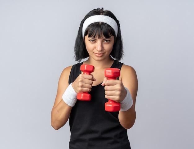 Jong fitnessmeisje met een hoofdband met halters die oefeningen doen die zelfverzekerd over een witte achtergrond staan