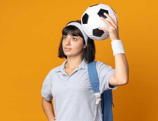 Jong fitnessmeisje met hoofdband met rugzak die voetbal vasthoudt en verbaasd opzij kijkt