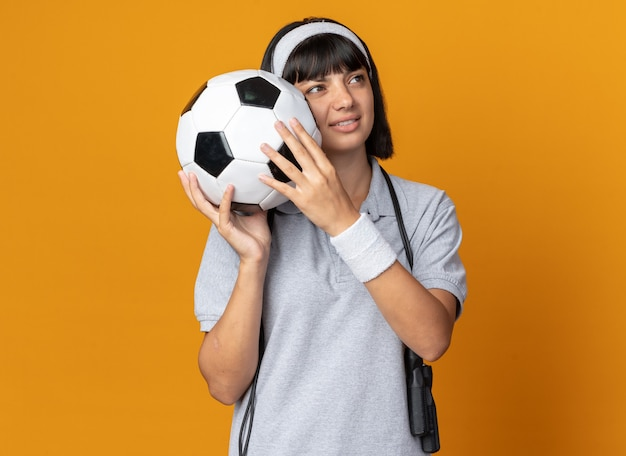 Jong fitnessmeisje met hoofdband met springtouw om nek met voetbal en kijken opzij, ontevreden over oranje achtergrond