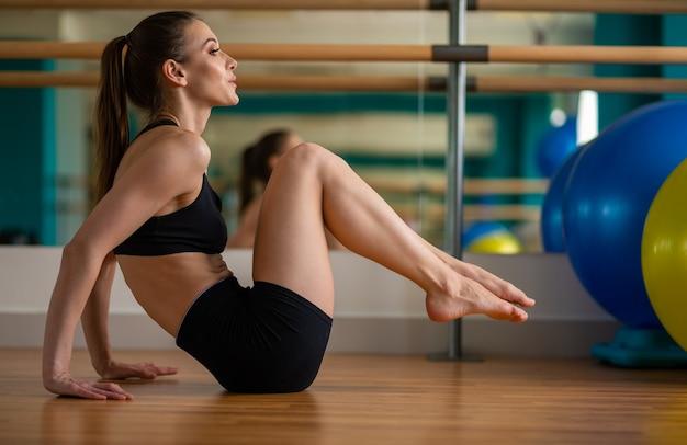 Jong fitnessmodel strekt zich uit in een fitnessclub foto van hoge kwaliteit