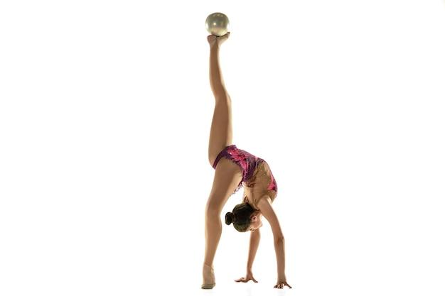 Jong flexibel meisje dat op witte achtergrond wordt geïsoleerd. tiener vrouwelijk model als ritmische gymnastiekkunstenaar die met materiaal oefent.
