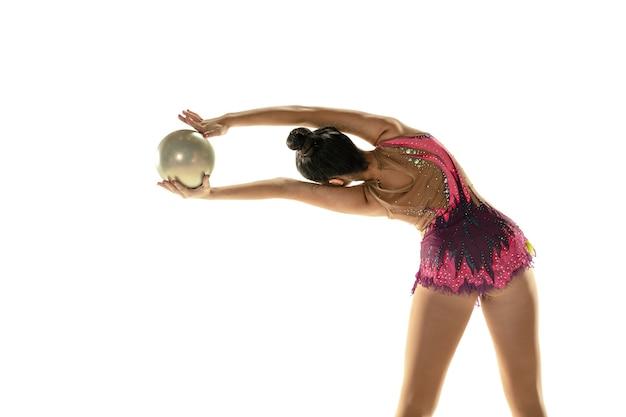 Jong flexibel meisje dat op witte muur wordt geïsoleerd. tiener vrouwelijk model als ritmische gymnastiekkunstenaar die met materiaal oefent. oefeningen voor flexibiliteit, balans. gratie in beweging, sport.