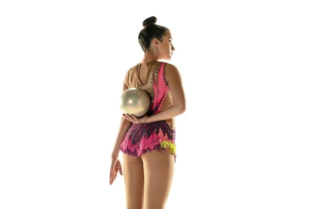 Jong flexibel meisje dat op witte studioachtergrond wordt geïsoleerd. tiener vrouwelijk model als ritmische gymnastiekkunstenaar die met materiaal oefent. oefeningen voor flexibiliteit, balans. genade in beweging, sport.