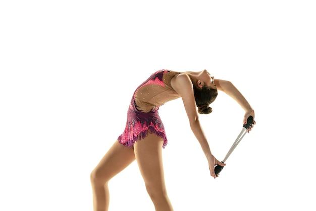 Jong flexibel meisje dat op witte studioachtergrond wordt geïsoleerd. tiener vrouwelijk model als ritmische gymnastiekkunstenaar die met materiaal oefent. oefeningen voor flexibiliteit, balans. genade in beweging, sport. Premium Foto