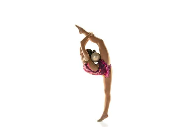 Jong flexibel meisje dat op witte studiomuur wordt geïsoleerd