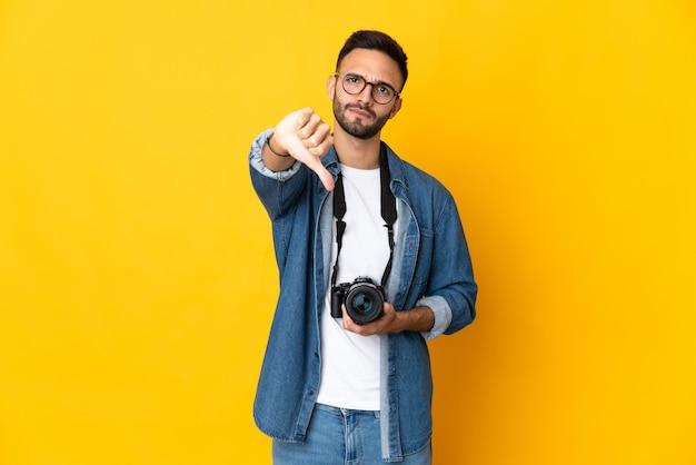 Jong fotograafmeisje dat op gele achtergrond wordt geïsoleerd die duim met negatieve uitdrukking toont