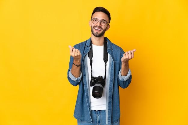 Jong fotograafmeisje dat op gele achtergrond wordt geïsoleerd die geldgebaar maakt